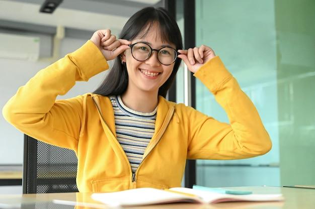 Азиатская студентка с стеклами и улыбнулась для камеры. она читает книги по подготовке к экзаменам. Premium Фотографии