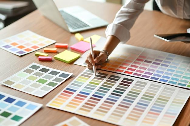 Архитектор сравнивает диаграмму цвета и использует планшет. Premium Фотографии