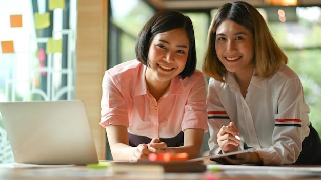 オフィスで一緒に働くアジアの女性グラフィックデザイナー彼らはラップトップとタブレットを使用します。 Premium写真