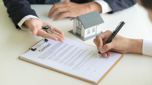 Концепция недвижимости, клиент подписывает контракт о договоре ипотечного кредита. Premium Фотографии