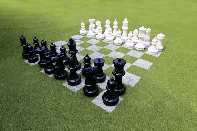 チェス盤と庭のチェスの駒 Premium写真