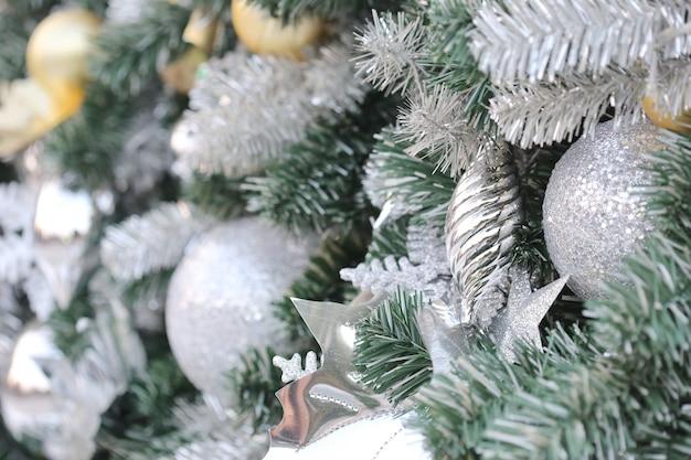 緑の松の木にゴールドカラーのクリスマスボールを掛ける Premium写真