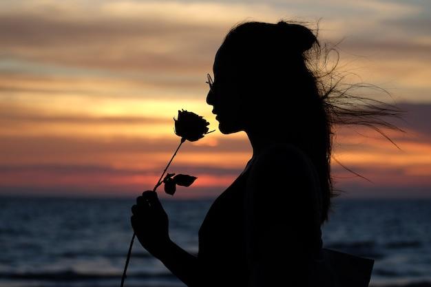 かなり若いシルエットの女性バレンタインデーでバラの香りがしています Premium写真