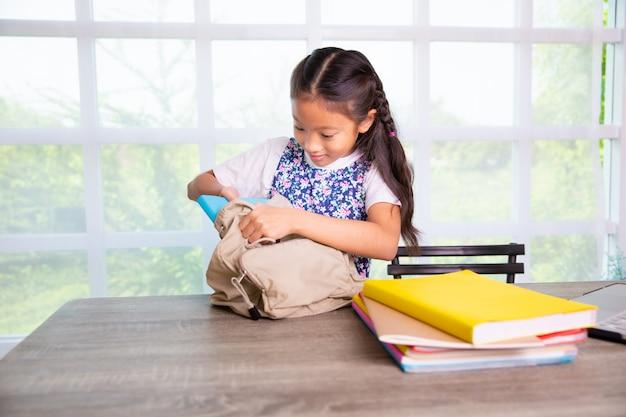 Ученица начальной школы упаковывает книги в сумки Premium Фотографии