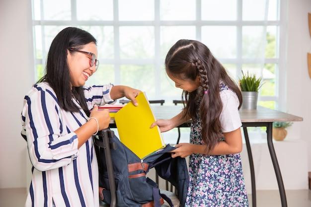 Мать помогает девочке начальной школы упаковывать книги в сумки Premium Фотографии