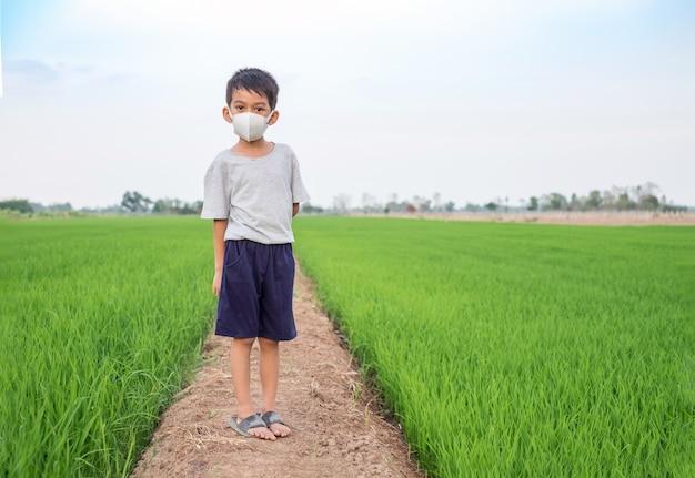 Азиатский лицевой щиток гермошлема носки мальчика стоя на ферме риса. здоровая концепция Premium Фотографии