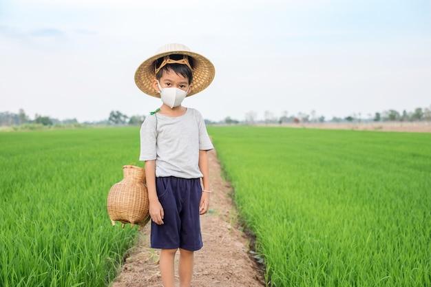 Азиатская маска для лица носки мальчика и бамбуковая шляпа при ловушки рыб стоя на ферме риса. здоровая концепция Premium Фотографии