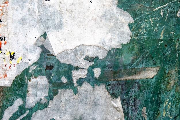 裂かれたステッカーペーパーとカラフルな壁からの抽象的な背景。 Premium写真