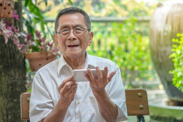 屋外でスマートフォンを使用して幸せな高齢者アジア老人。 Premium写真