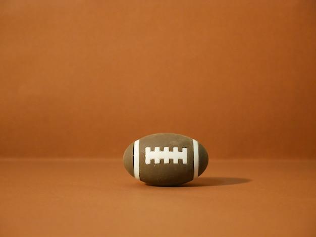 茶色の背景にコピースペースを持つアメリカンフットボール Premium写真