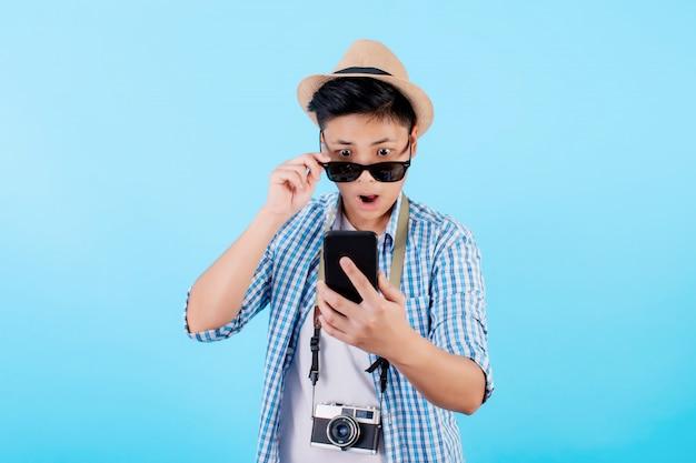 Туристы с удивлением получают поразительные новости на своих смартфонах в дороге. шокирующие азиатские туристы в летней повседневной одежде с отдельными камерами на синем фоне. путешественники за границей на отдыхе Premium Фотографии