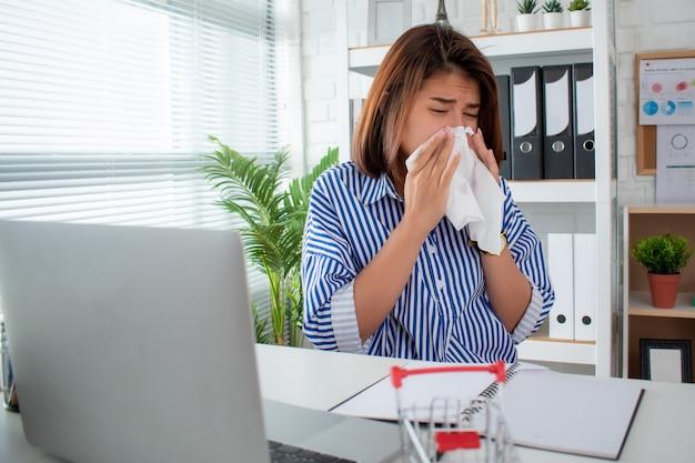 Азиатская коммерсантка имеет чихать и кашлять на ее столе в офисе. Premium Фотографии