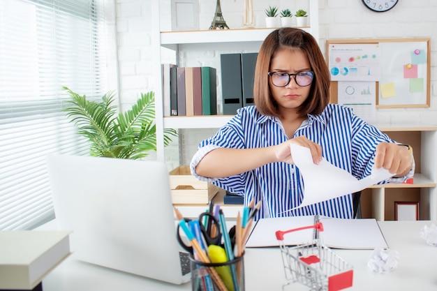 紙を引き裂くアジア女性実業家 Premium写真