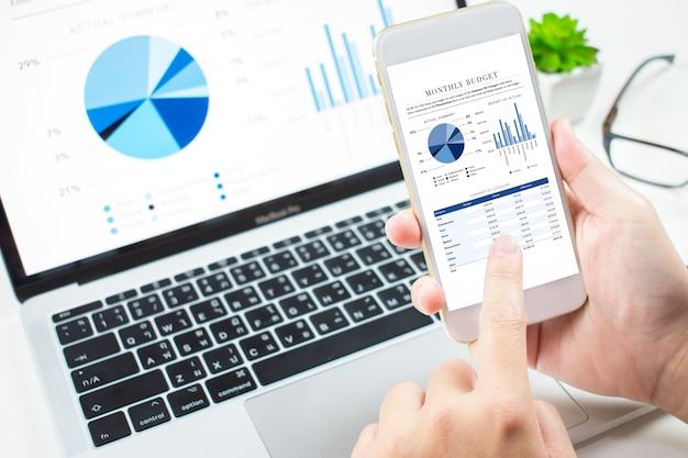 投資家は電話機の財務ダッシュボードで市場への投資を分析します Premium写真