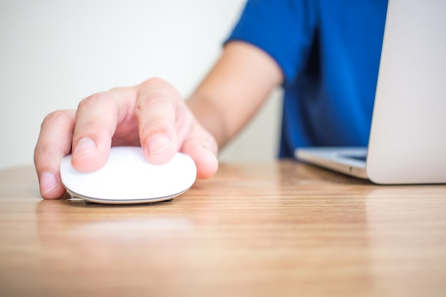 ノートパソコンでマウスを使って青いシャツを着た男の手のクローズアップショット。 Premium写真