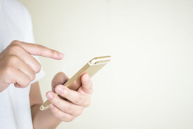 白いシャツを着ている女性の手は、電話でソーシャルメディアを使っています。 Premium写真