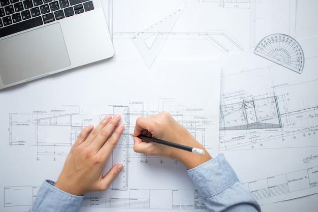 エンジニアは机の上に建物のレイアウトを描いています。 Premium写真