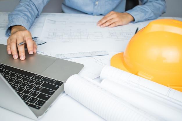 エンジニアの手が机の上に家の計画を作成していたコンピューターに取り組んで Premium写真