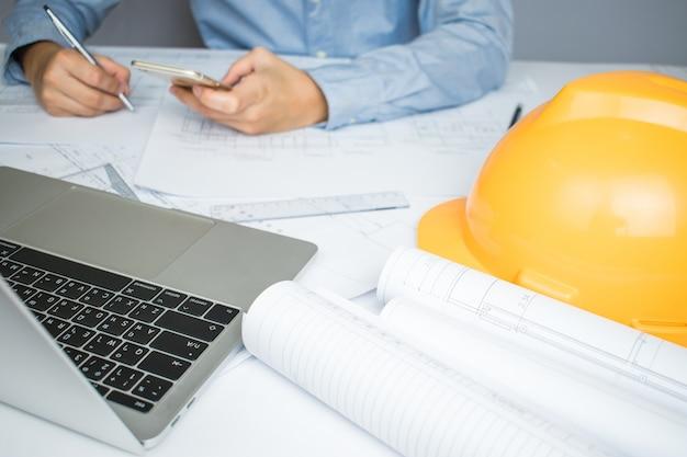 ラップトップ上で通信する建築家エンジニアの手 Premium写真