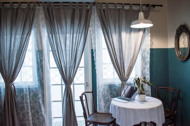 Картины компьютеров, размещенных на деревянных столах рядом с большими окнами. Premium Фотографии
