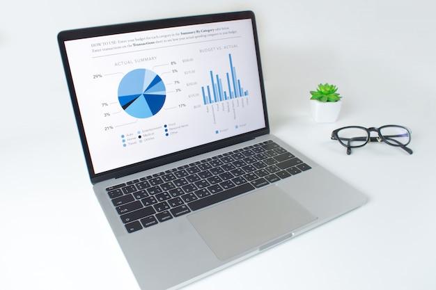 財務統計レポートとラップトップコンピューターを備えたモダンな白いテーブル Premium写真