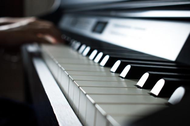 ミュージシャンは音楽練習室でピアノを弾いています。 Premium写真
