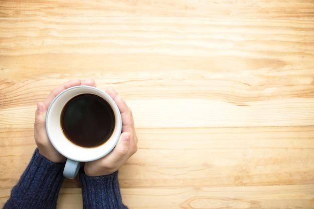彼女の手で一杯のコーヒーを保持している青いジャージを着ている女性。 Premium写真