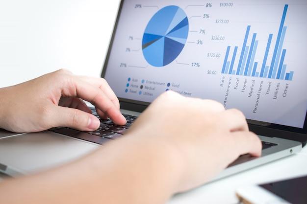 ビジネスマンはラップトップを使用して統計を分析します。 Premium写真