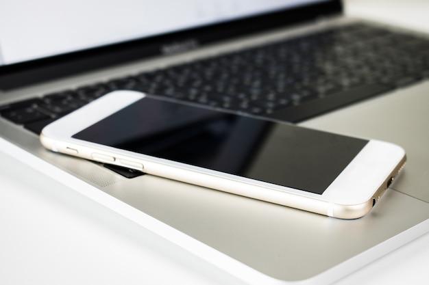 ノートパソコンの机の上のクローズアップスマートフォン。 Premium写真