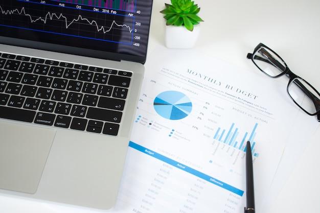 オフィスワーカーの近代的な机の上のラップトップコンピューターの財務グラフ。 Premium写真