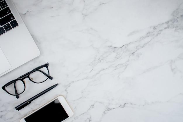 大理石のテーブルで作業するためのアクセサリーと現代の職場で働くビジネス。 Premium写真