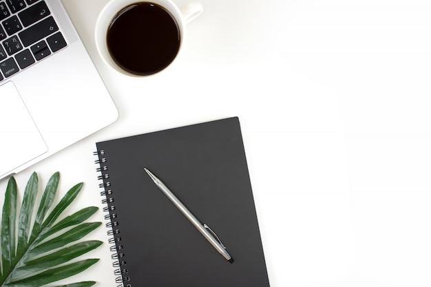 白い色でフラット横たわっていた、トップビューオフィス現代作業テーブル。アクセサリーはラップトップ、ノートブック、ペン、コーヒー、コピースペース付きの緑の葉で白い色で動作します Premium写真