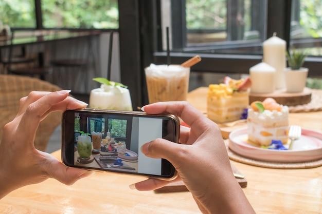 若い女性はレストランでスマートフォンでケーキを取っています。 Premium写真