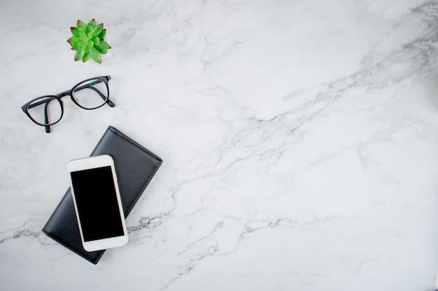 黒い革製の財布、メガネ、植物にスマートフォンを備えた大理石のデスク Premium写真