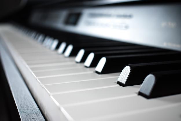 音楽室の黒いピアノのキーのクローズアップ。 Premium写真