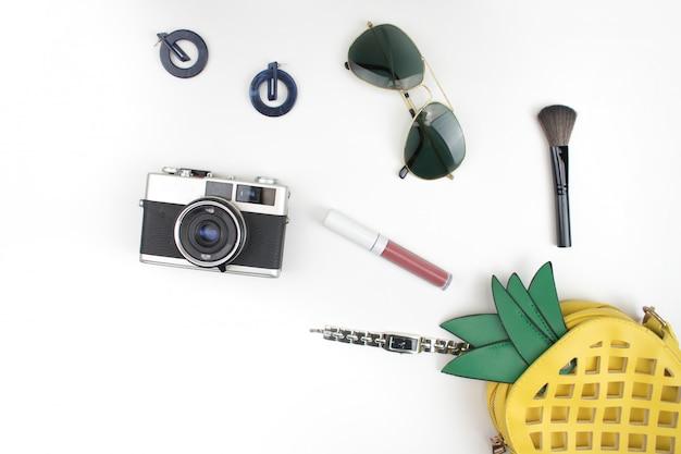 黄色のパイナップルバッグは、白地に化粧品、アクセサリー、時計、サングラス、フィルムカメラで開きます。平干し。 Premium写真