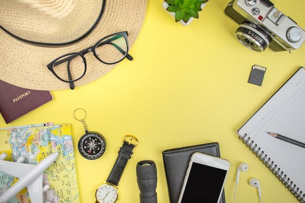 旅行のコンセプト。帽子、メガネ、ビンテージカメラ、パスポート、地図、ノートブック、スマートフォン、時計、コンパス、コピースペースと黄色の背景の財布と旅行アクセサリー。 Premium写真