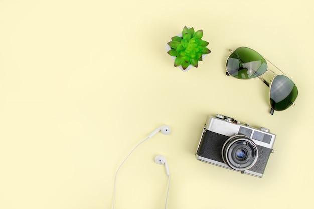 フィルムカメラ、サングラス、黄色の背景との休日。上面図。 Premium写真