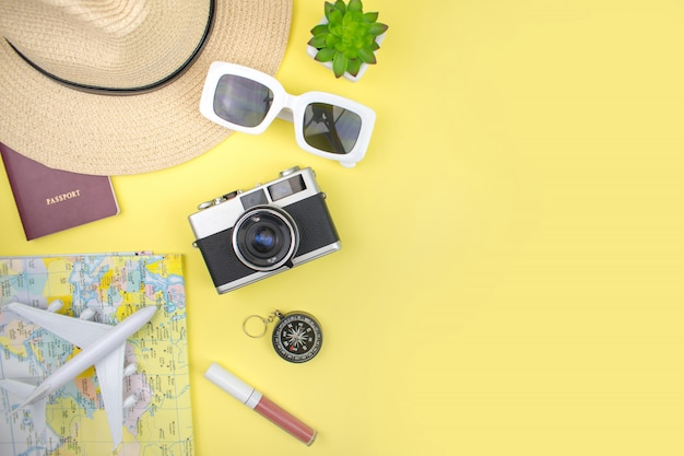 黄色の背景に帽子、地図、スマートフォン、フィルムカメラ、サングラスをかけた少女の休暇。上面図。 Premium写真