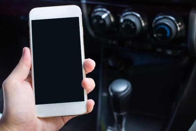 旅行のために車の中でスマートフォンを持っている手のクローズアップ。コピースペース付き。 Premium写真
