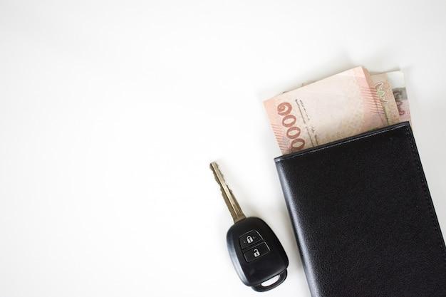 車のキーのトップビューで財布にお金 Premium写真