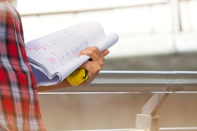 働く女性は青写真と測定テープを保持しています。 Premium写真