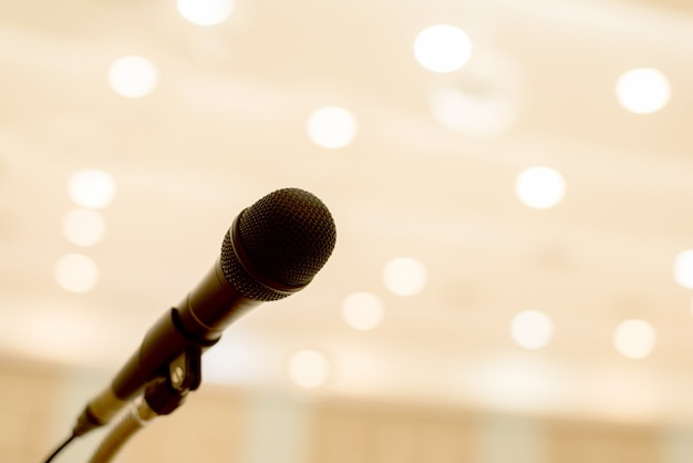 マイクは、会議室またはセミナー室の表彰台の上にボケの光があります。 Premium写真