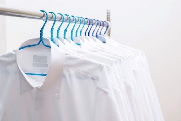 行のラックに掛かっている白いシャツ Premium写真