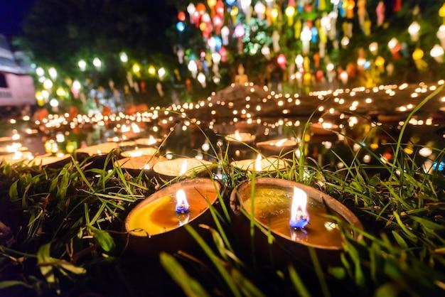 ボケ味を持つ夜のタイの寺院でビンテージスタイルのキャンドルカップ Premium写真