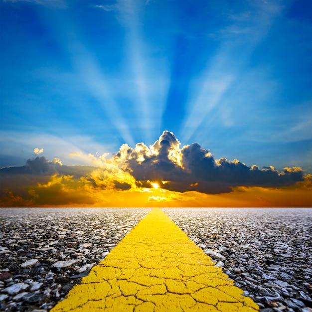 Вдоль дороги с закатом небо и солнечные лучи фон Premium Фотографии