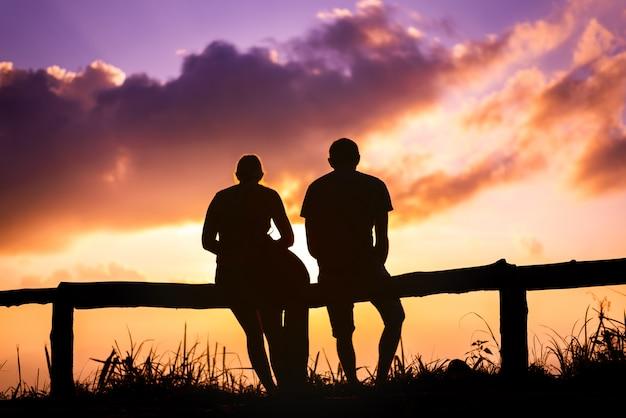 Любовник пар силуэта с ландшафтом гор в красивом небе захода солнца Premium Фотографии