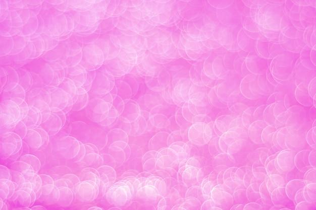 キラキラ光の抽象的なピンクのボケ Premium写真