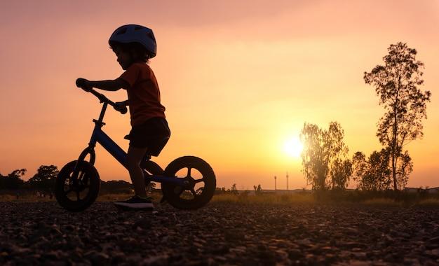 シルエットアジアの子供の初日はバランスバイクをプレイ。 Premium写真