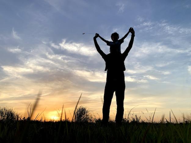 日没時に空に対して息子を運ぶシルエット父 Premium写真